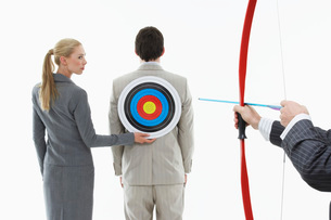 Business woman holding target to man's back while other manの写真素材 [FYI03642088]