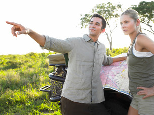 Couple on safari man pointing map on jeepの写真素材 [FYI03642107]