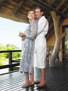 Adult couple in bathrobes embracing on terraceの写真素材 [FYI03642114]