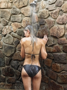 Young woman having shower by stone wall back view outdoorsの写真素材 [FYI03642117]