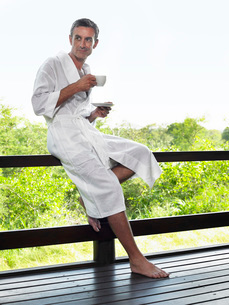 Adult man in bathrobe leaning on terrace railing holding cupの写真素材 [FYI03642118]