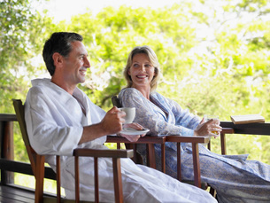 Adult couple sitting on terrace man holding cup smilingの写真素材 [FYI03642121]