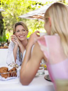 Two women sitting at table having conversation selective focの写真素材 [FYI03642129]