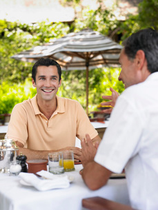 Two men having conversation at table laughing selective focuの写真素材 [FYI03642133]
