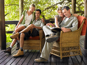 Two couples sitting on terrace smiling one man readingの写真素材 [FYI03642134]