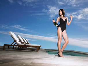 Woman in bathing suit holding champagne at poolsideの写真素材 [FYI03642152]