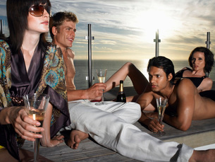 Young people drinking champagne on pool deck near sea at sunの写真素材 [FYI03642158]