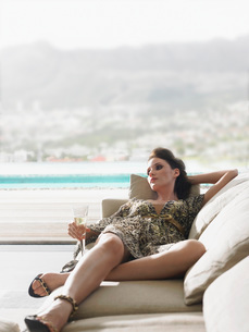 Woman reclining on sofa with champagne on balconyの写真素材 [FYI03642164]