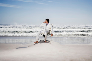 Man using mobile phone sitting on office chair on beachの写真素材 [FYI03642192]