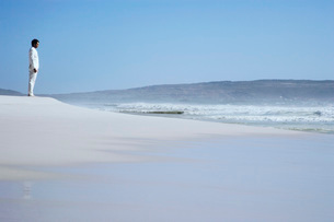 Man standing on sand dune on beach side viewの写真素材 [FYI03642194]