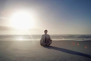 Business man sitting in lotus pose on beachの写真素材 [FYI03642197]