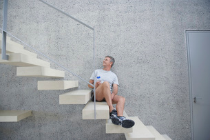 Smiling mid-adult man sitting on staircase holding bottle ofの写真素材 [FYI03642207]