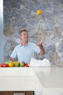 Mature man throwing orange into air standing at kitchen counの写真素材 [FYI03642215]