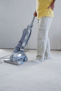 Mature man vacuuming carpet holding lower back in pain low sの写真素材 [FYI03642219]