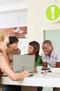 Four people having meeting around laptop.の写真素材 [FYI03642240]