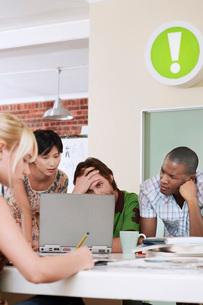 Four people having meeting around laptop.の写真素材 [FYI03642246]