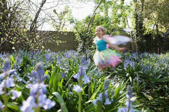 Young girl (5-6) running in flower garden wearing fairy costの写真素材 [FYI03642283]