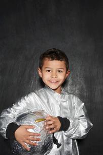 Portrait of young boy (5-6) in astronaut costume holding helの写真素材 [FYI03642305]