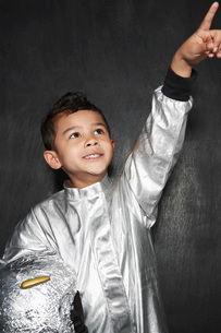 Portrait of young boy (5-6) in astronaut costume pointing upの写真素材 [FYI03642306]