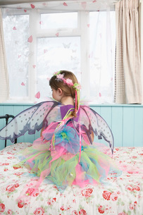 Young girl (5-6) wearing fairy costume sitting on bed by winの写真素材 [FYI03642308]