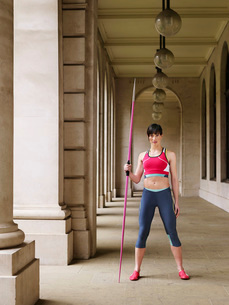 Female athlete holding javelin standing in portico portraitの写真素材 [FYI03642312]