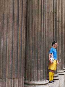 Soccer player holding ball standing between columns side vieの写真素材 [FYI03642318]