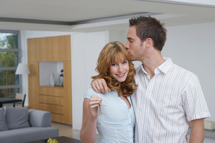 Couple embracing woman holding key in new homeの写真素材 [FYI03642334]