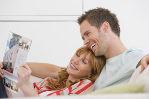 Couple reading brochure on sofaの写真素材 [FYI03642335]