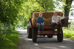 Two boys (5-6 7-9) sitting on back of trailer on country lanの写真素材 [FYI03642345]