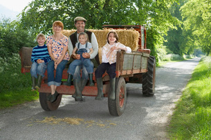 Parents with three children (5-9) sitting on trailer on counの写真素材 [FYI03642348]