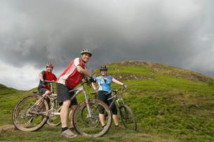 Three cyclists on hillside portraitの写真素材 [FYI03642422]