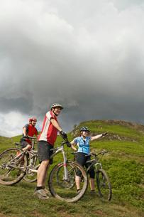 Three cyclists on hillsideの写真素材 [FYI03642424]