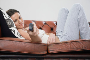 Young woman holding remote control lying on sofaの写真素材 [FYI03642459]