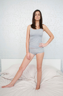 Young woman in underwear standing on bed portraitの写真素材 [FYI03642464]