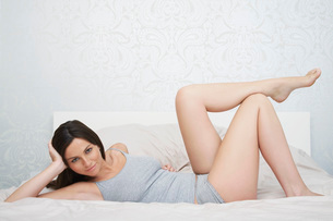 Young woman in underwear lying on bed portraitの写真素材 [FYI03642465]