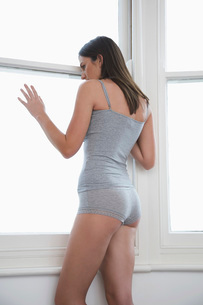Young woman in underwear looking out of bedroom windowの写真素材 [FYI03642472]