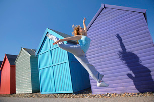 Woman jumping in front of beach hutsの写真素材 [FYI03642528]