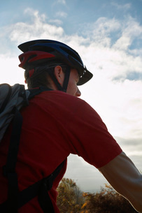 Mountain biker looking at view in countrysideの写真素材 [FYI03642550]