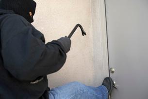Burglar kicking door of houseの写真素材 [FYI03642574]