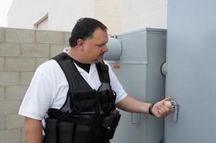 Security guard checking padlockの写真素材 [FYI03642613]