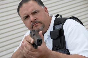 Portrait of security guard in bulletproof vest holding gunの写真素材 [FYI03642622]
