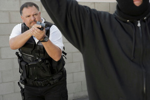 Security guard aiming gun at thiefの写真素材 [FYI03642631]