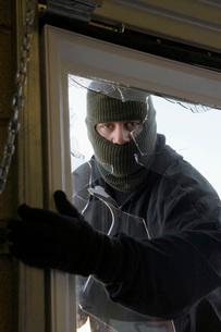 Masked thief braking in through windowの写真素材 [FYI03642636]