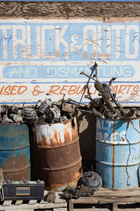 Rusty sign and barrels in junkyardの写真素材 [FYI03642668]