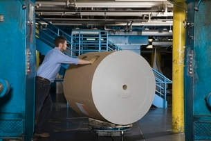 Man pushing huge roll of paper in newspaper factoryの写真素材 [FYI03642795]