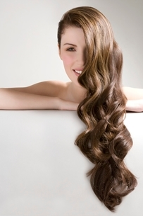 Woman with long brown wavy hairの写真素材 [FYI03642864]