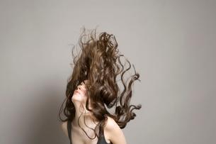 Woman tossing long brown wavy hairの写真素材 [FYI03642867]