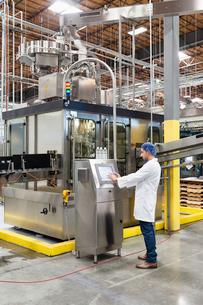 Man working on machinery in bottling industryの写真素材 [FYI03642952]