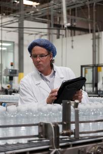 Man at bottling plant inspecting bottled water on conveyorの写真素材 [FYI03642955]