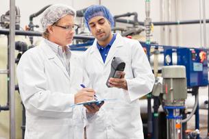 Two men working in bottling factoryの写真素材 [FYI03642961]